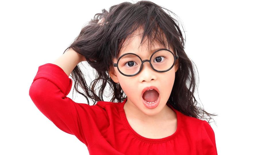 Une petite fille à l'air embêté se gratte la tête.