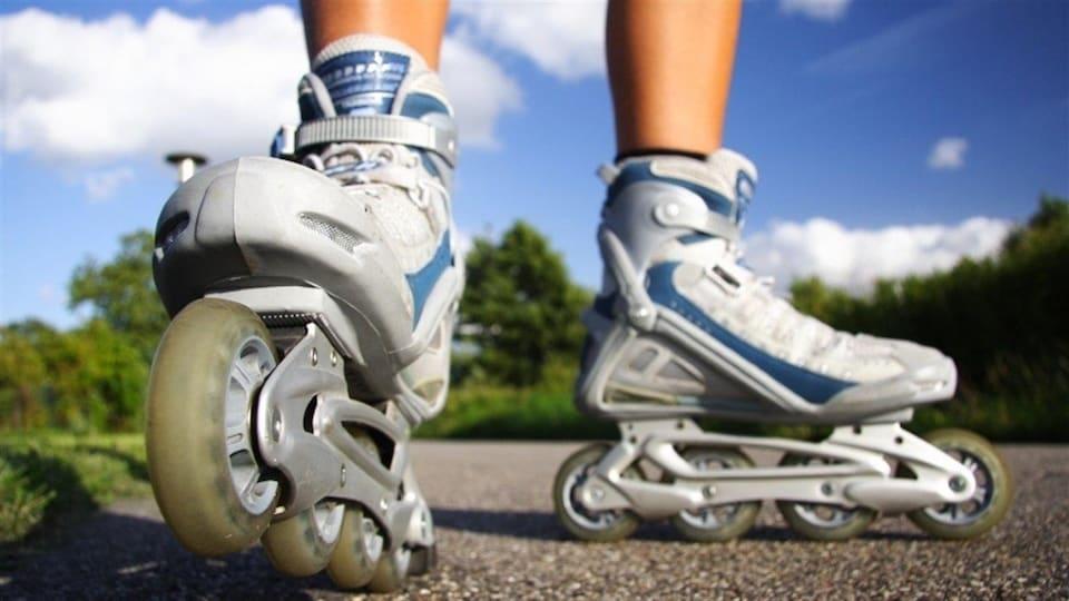 Gros plan sur des pieds chaussés d'une paire de patins a roues alignées sur un sentier pavé dans un parc boisé.