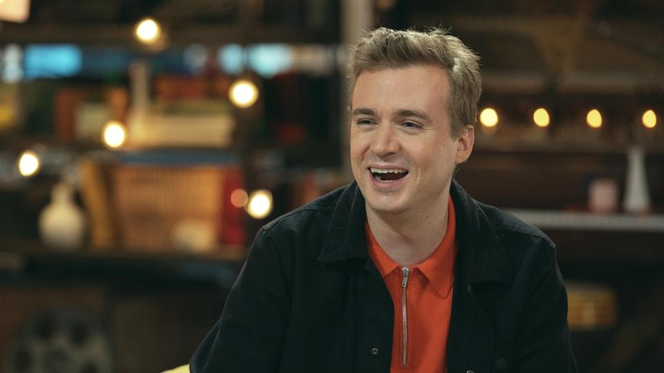 Il est sur le plateau d'une émission de télé et rigole, assis.