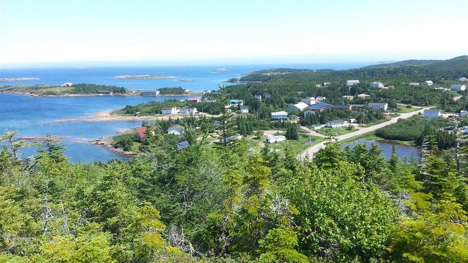 Vue panoramique estivale d'un village sur le bord du fleuve Saint-Laurent.