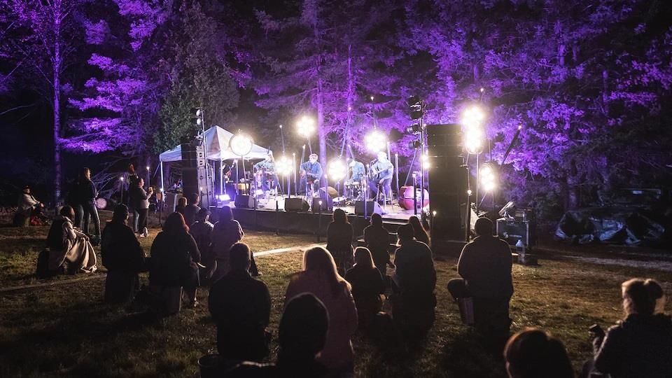 Un groupe en spectacle le soir, devant une foule en distanciation sociale.