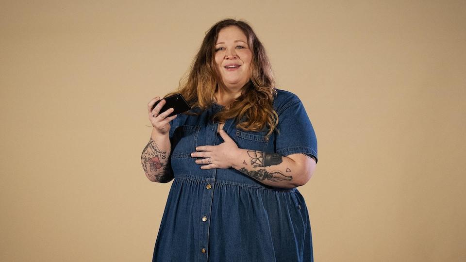 La militante grosse, Gabrielle Lisa-Collard, tient un téléphone devant un fond beige dans le bunker pour parler de grossophobie.