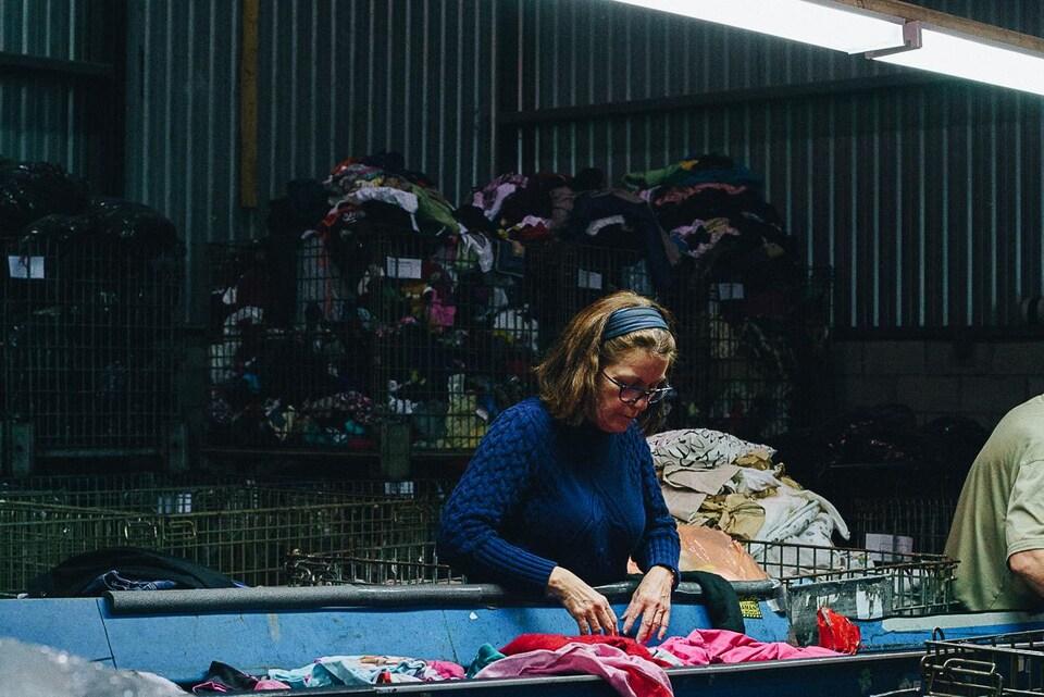 Une femme trie des vêtements usés chez Certex, un des plus gros centres de tri au Québec, à Longueuil.