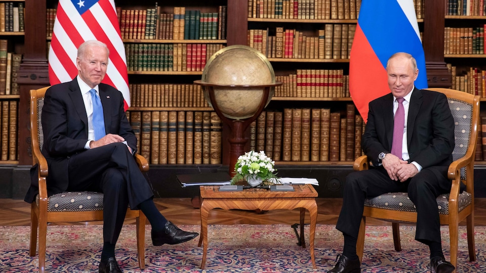 Joe Biden et Vladimir Poutine assis sur des chaises devant une bibliothèque.