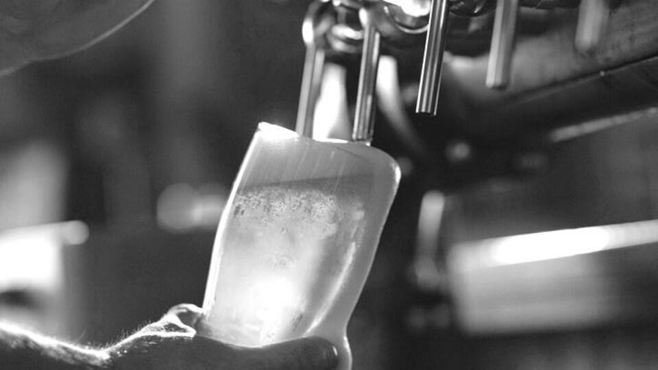 Un barman rempli une bière en fut.