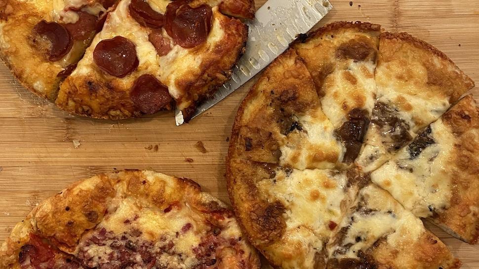 Trois pizzas sont déposées sur une planche de bois.