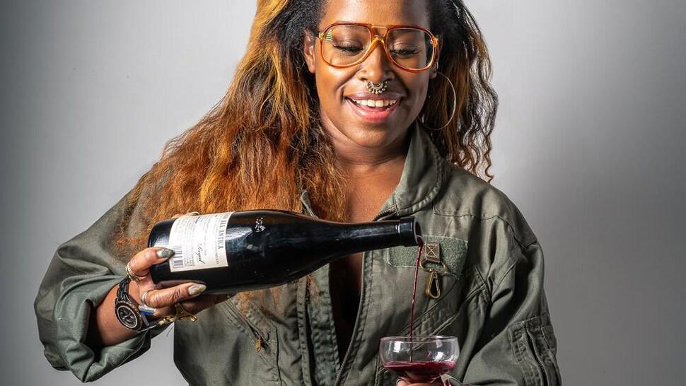 Ashtin Berry tient une coupe dans laquelle elle verse du vin.