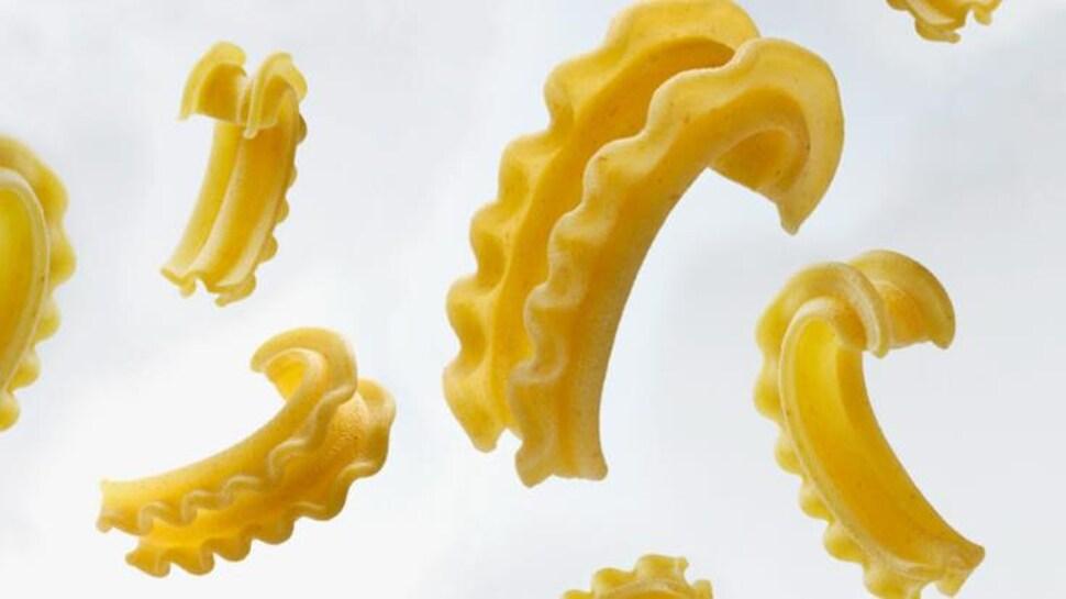 Sur un fond blanc, il y a plusieurs angles de la pâte. En forme d'arc, elle a des jabots comme une lasagne de chaque côté qui créent un creux pour la sauce.