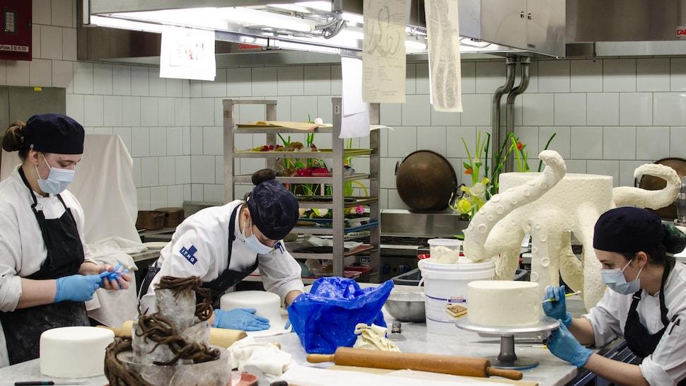 Dans une cuisine scolaire, trois étudiantes travaillent sur leur gâteau de mariage, dont un en forme de pieuvre géante.