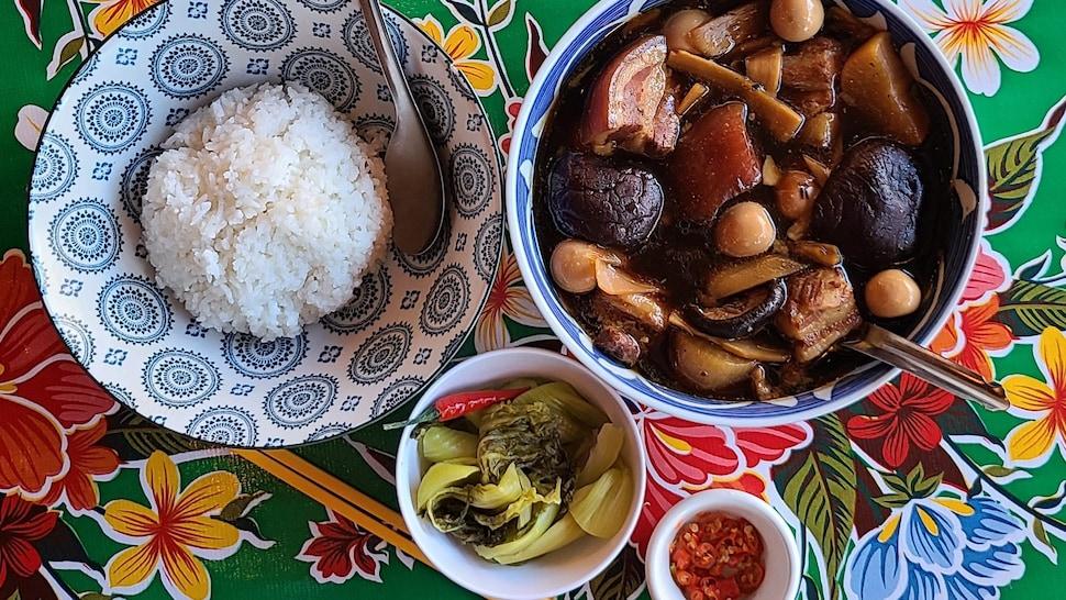 Un plat de Thit Kho servi avec du riz et des légumes dans divers bols.