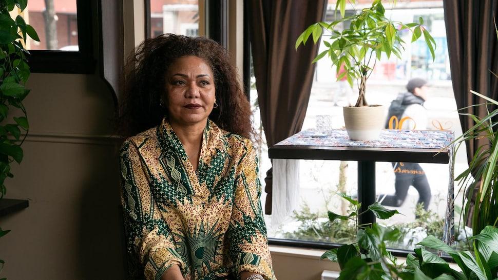 Maria-Josée de Frias est assise, entourée de plantes vertes, dans son restaurant.