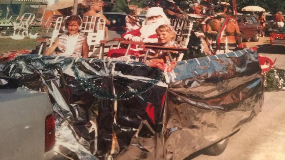 deux enfants assis sur des chaises pliantes dans un char allégorique avec un père Noël.
