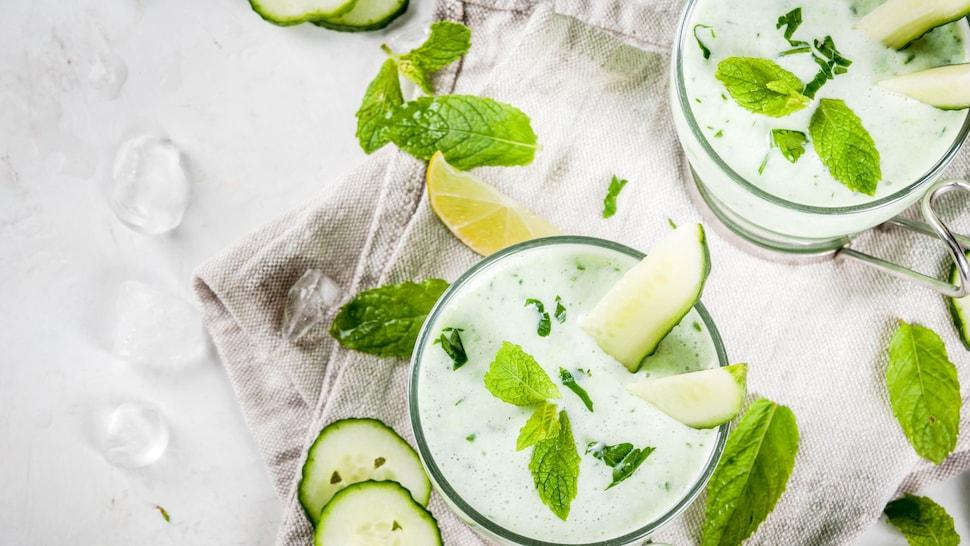 Deux soupes blanches dans des tasses en vitre avec des morceaux de concombres, de lime et de la menthe.
