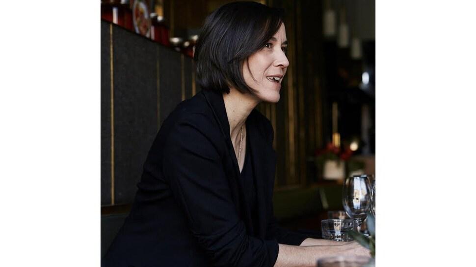 La sommelière Véronique Dalle est assise à la table d'un restaurant avec un verre de vin.