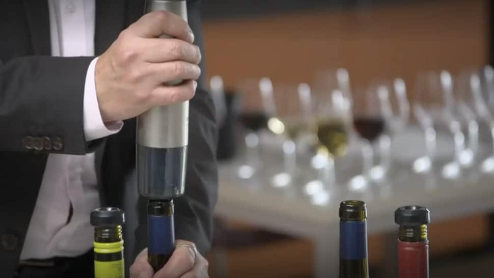 Une personne referme une bouteille de vin.