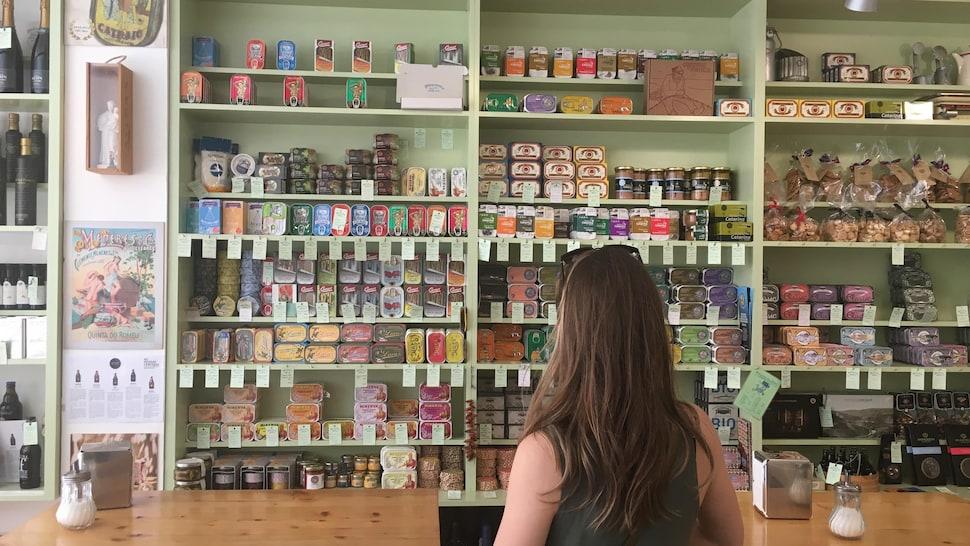 Dans une boutique un présentoir est rempli de conserve de sardines de différentes formes et de couleurs.