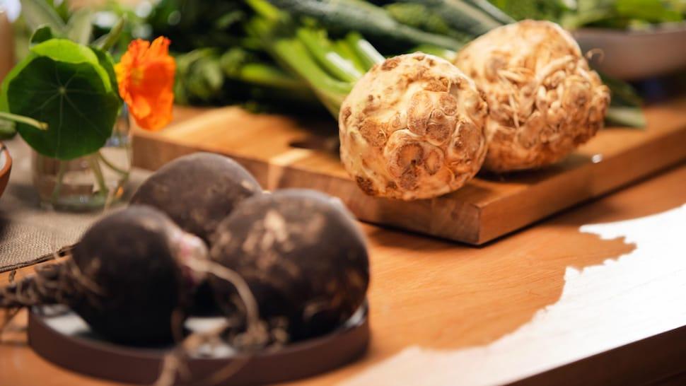 Sur un îlot de cuisine, des radis noirs et des céleris-raves sont prêts à être découpés pour la préparation d'un repas.