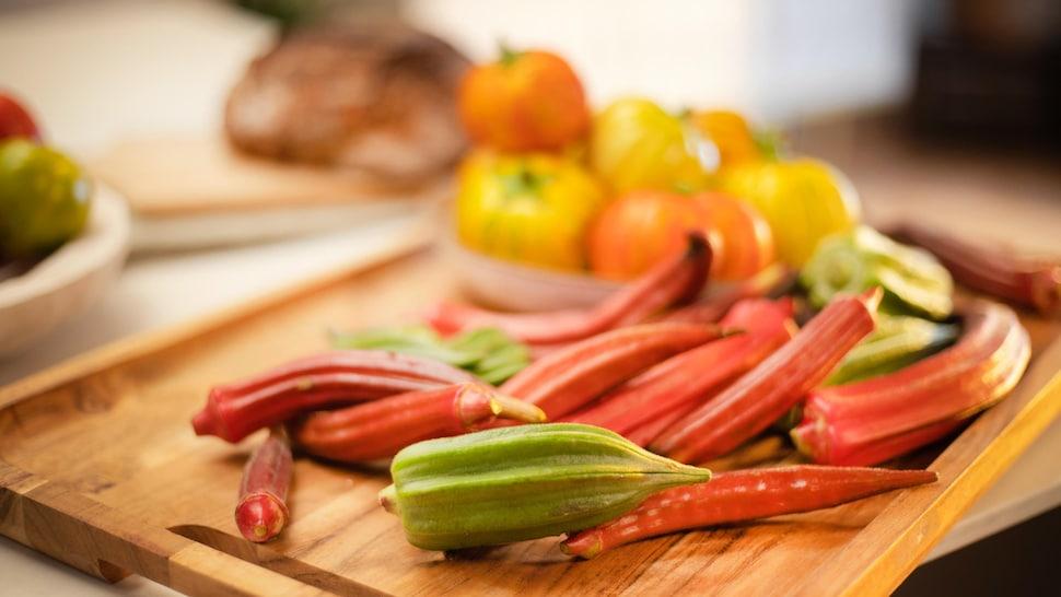 Des okras et des aubergines africaines sont sur une planche à découper.