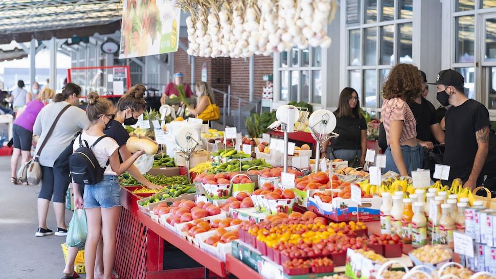 Des personnes achètent des légumes à un cultivateur.