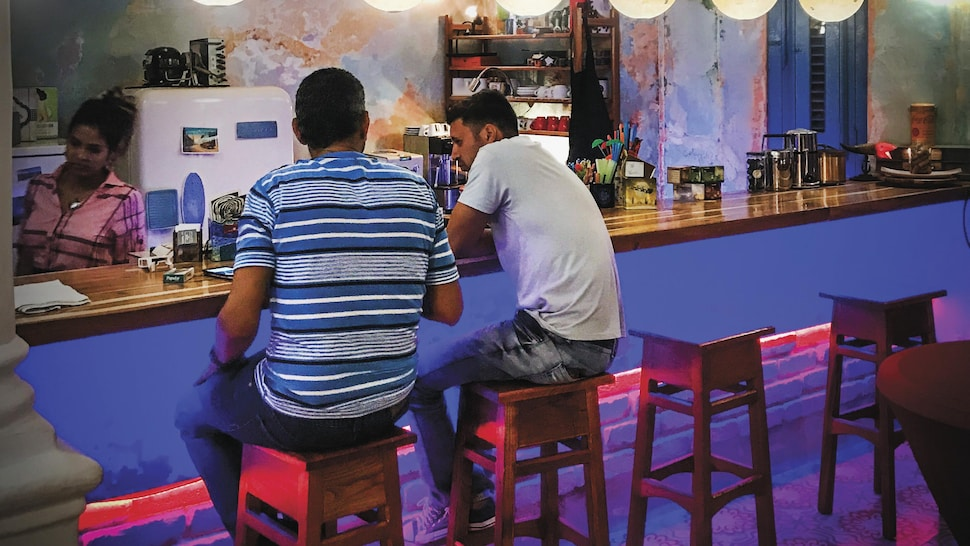 Deux clients sont assis au bar dans le café.