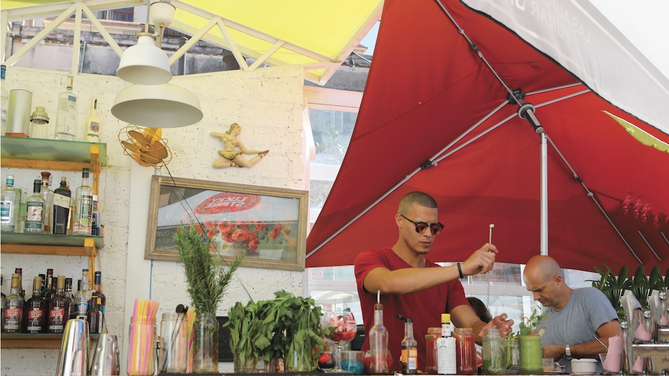 Derrière le bar, un employé touille un cocktail pour servir un client.