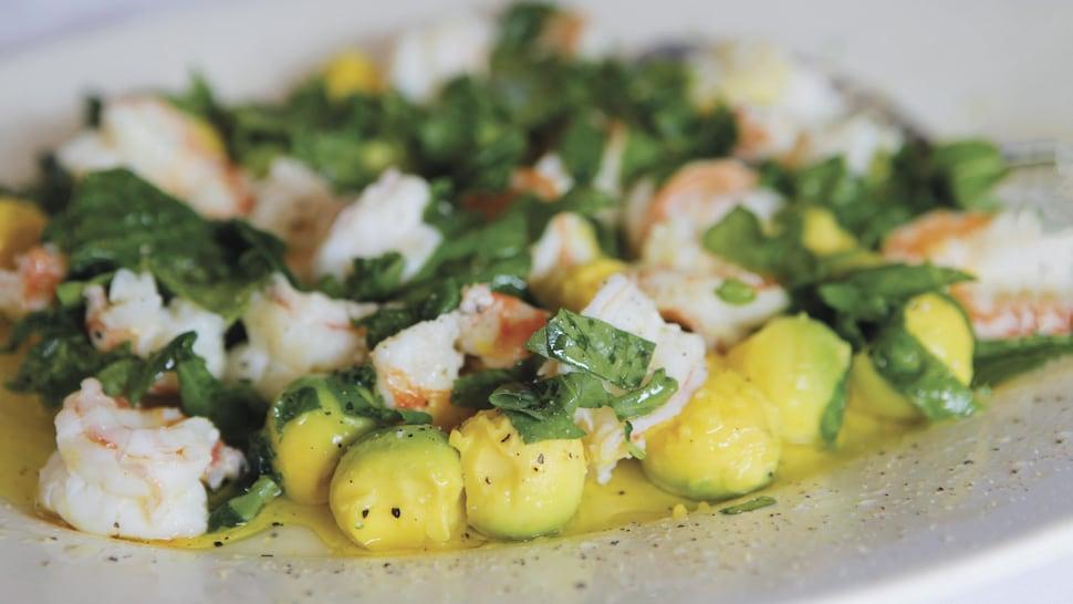 Dans une assiette ronde, des crevettes géantes avec des morceaux d'avocats nappés légèrement d'une vinaigrette.