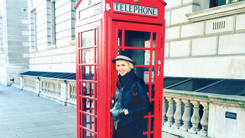 L'animatrice pose devant une cabine de téléphone dans une rue de Londres.