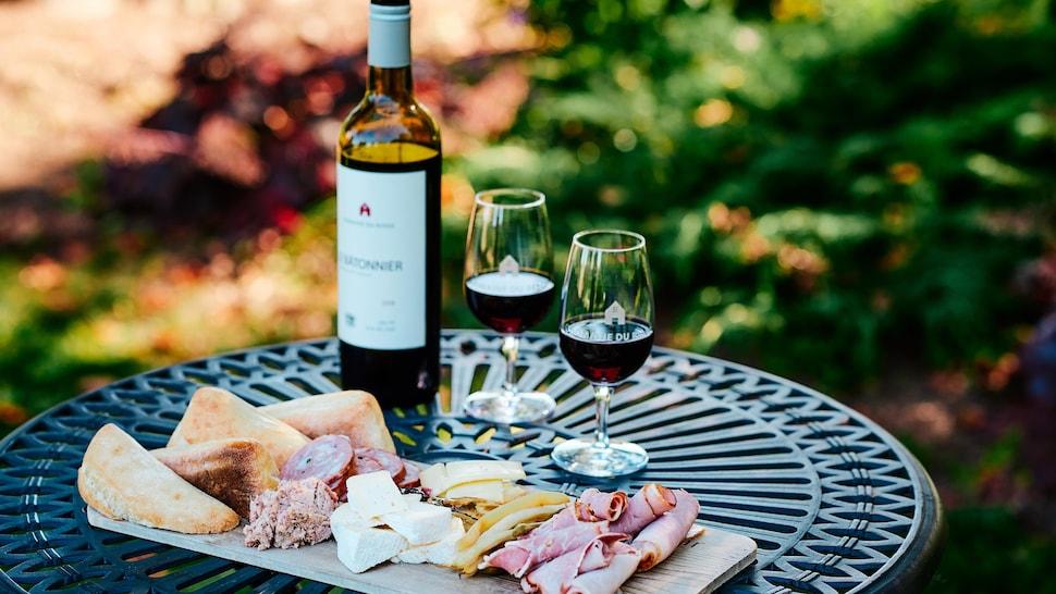 Sur une table de jardin, différentes tranches de viandes froides, des fromages et des morceaux de pain ont été déposés pour des clients.