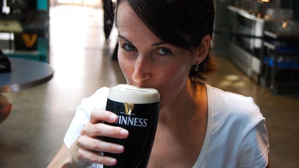 Geneviève O'Gleman qui boit un verre de Guinness.