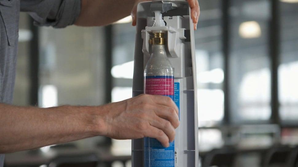 Une personne visse une bouteille de CO2 à sa machine.
