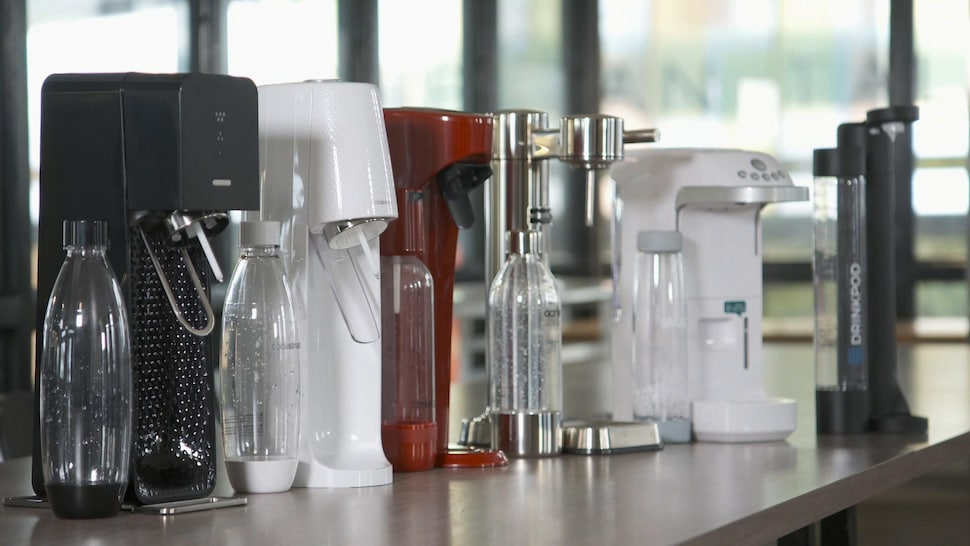 Six machines sont déposées sur une table dans un local de recherche.