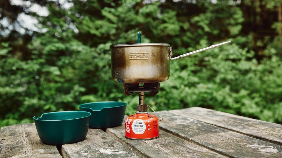 Sur un réchaud à gaz compact, est déposé une petite casserole en métal. Ceux sont déposé sur une table en bois ainsi que deux bols en plastique vert.