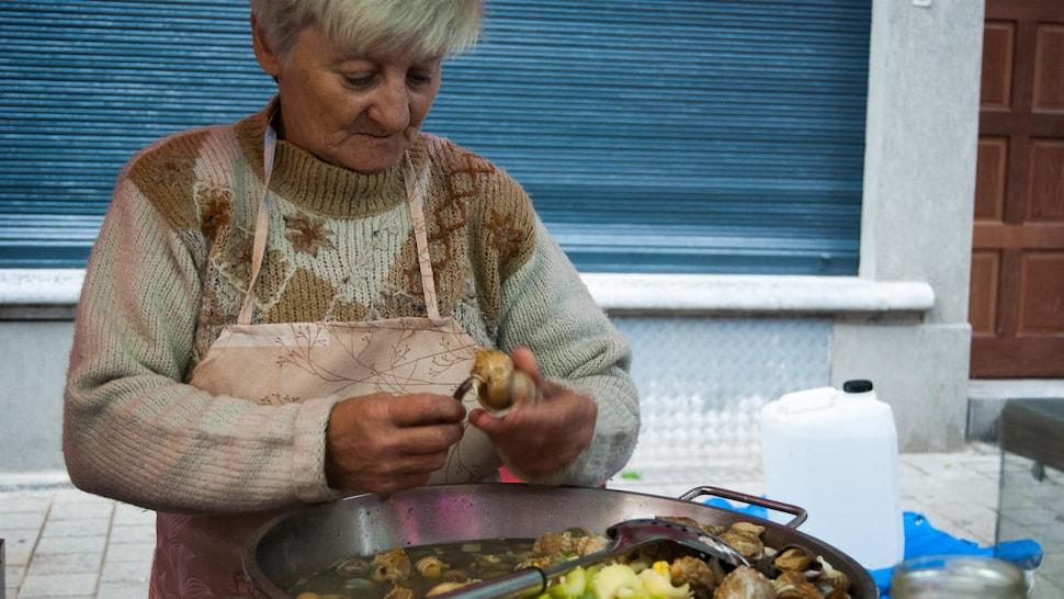 Femme qui prépare des caricoles à Bruxelles.