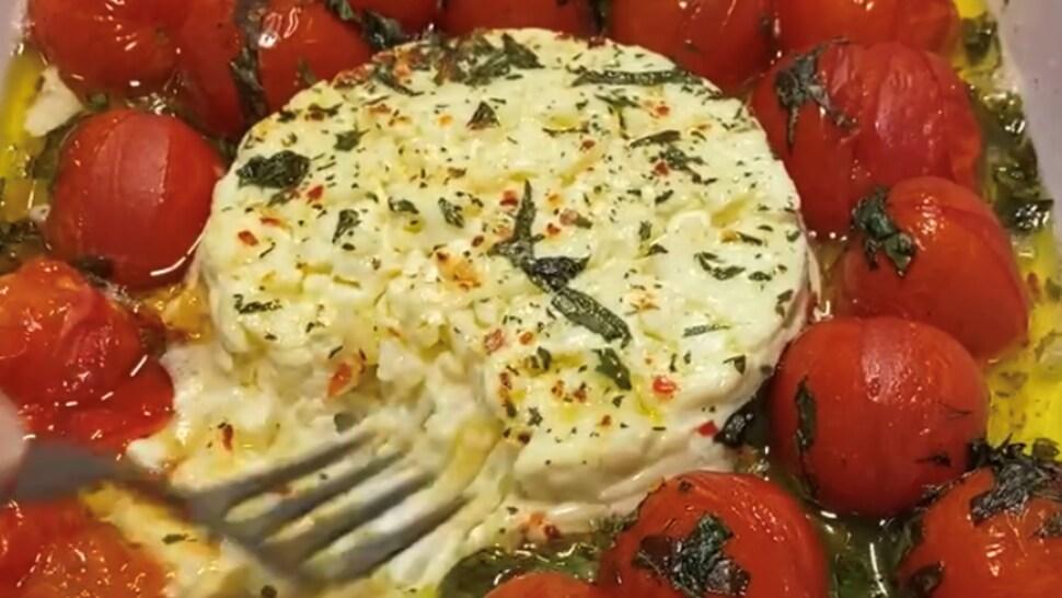 Dans une assiette carrée, une personne écrase du feta fondu pour le mélanger aux tomates cerises.