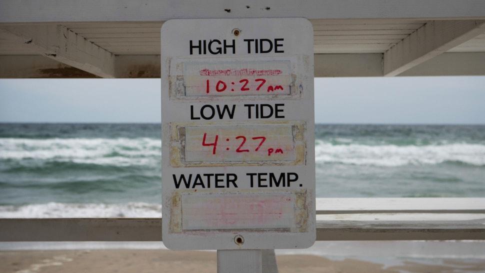 Un panneau sous une chaise de sauveteur face à la mer indique les heures et la température de l'eau.