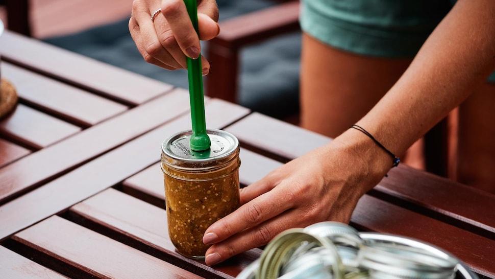 Femme qui dépose un disque de métal sur un pot de conserve en verre.