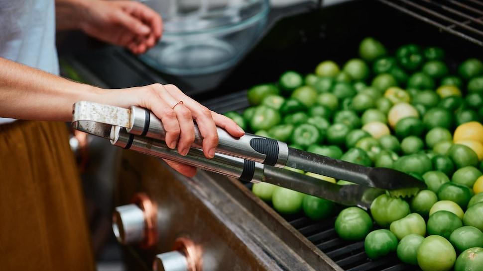 Femme qui tourne des tomates vertes sur un barbecue.