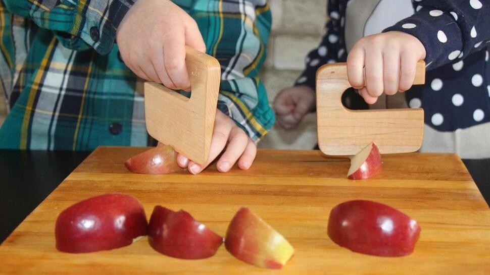 Deux tout-petits qui coupent des quartiers de pommes avec un couteau en bois.
