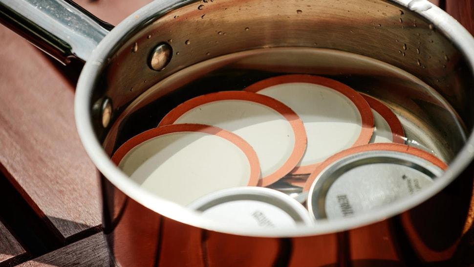Disques de métal pour pots de conserves dans une casserole remplie d'eau.
