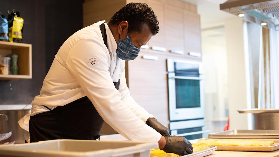 Un homme coupe en cubes des oeufs cuits.