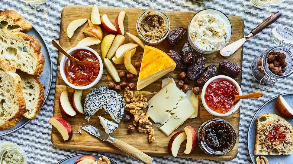 Planche de bois avec des fruits, es noix, des pâtés, des fromages et des gelées.