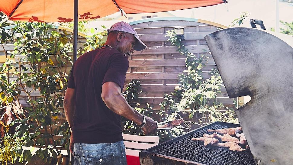 Martiniquais qui fait cuire de la viande sur un grill.