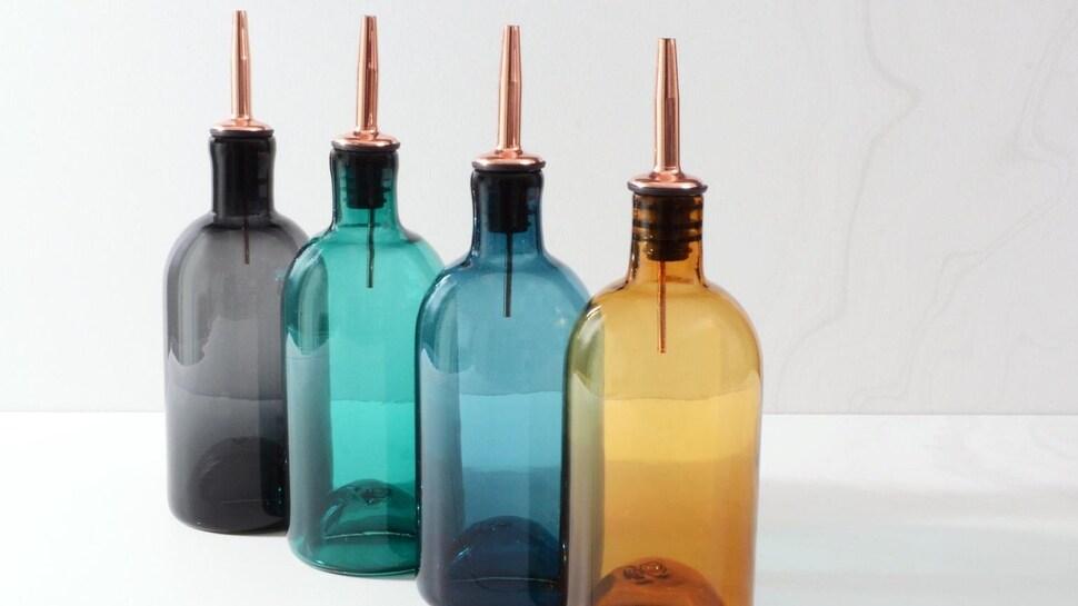 Quatre bouteilles de huilier en verre coloré fait à la main.