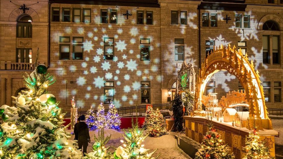 Des visiteurs admirent des faisceaux de lumière en forme d'étoiles projetés sur le mur d'un bâtiment.