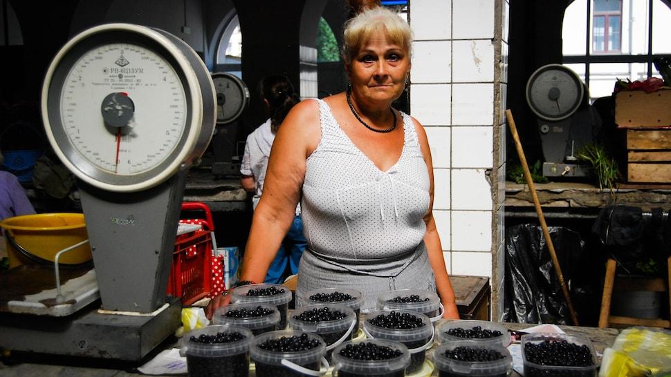 Femme devant les fruits qu'elle vend dans un marché russe.
