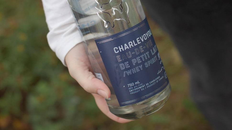 La bouteille d'eau-de-vie dans les mains d'une personne.
