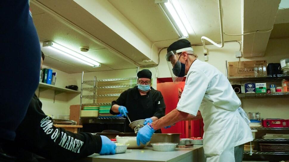 Paul Bergeron cuisine en compagnie d'autres personnes.