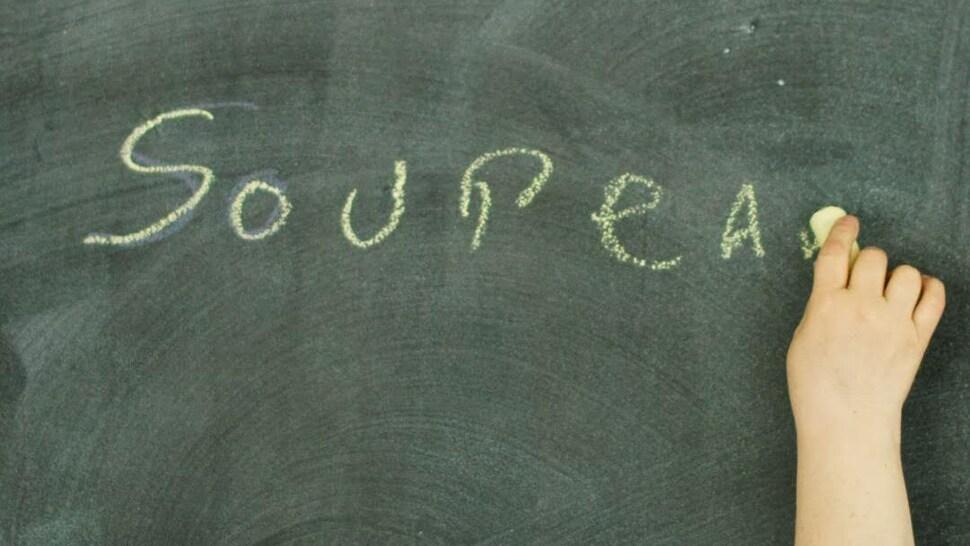 Une personne écrit le menu du jour sur un tableau noir.
