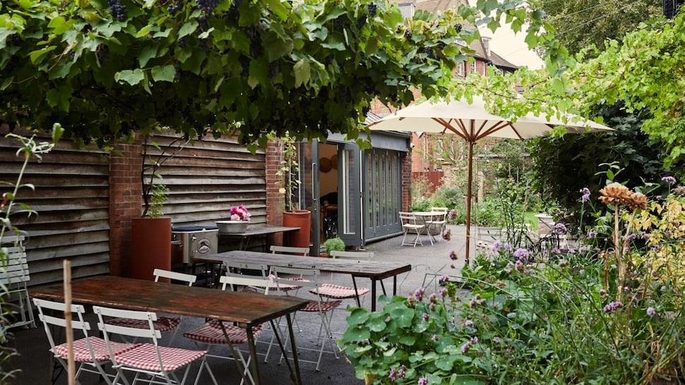 Dans une cour intérieure, des tables en bois et un parasol forment la terrasse du restaurant.