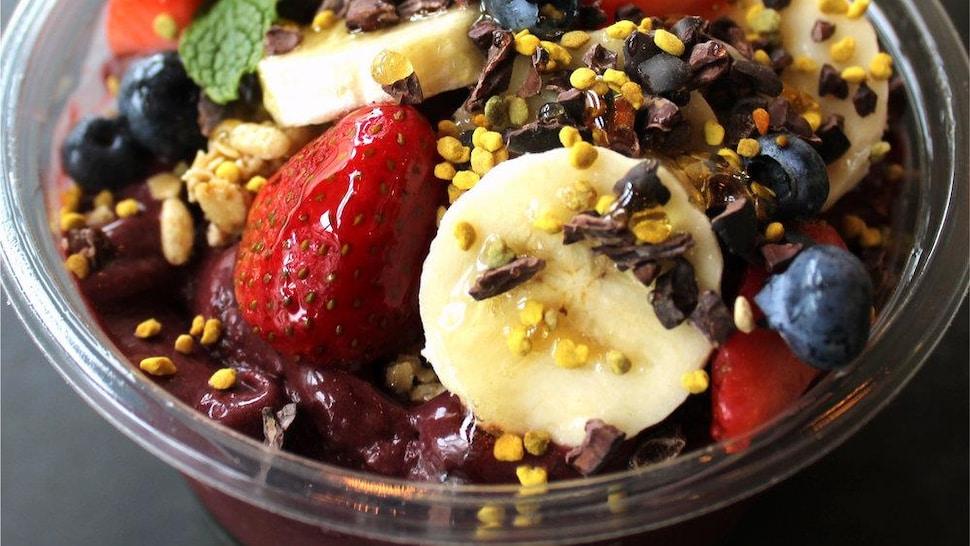Dans une coupe de verre, des petits fruits et granolas  est posée sur une surface.